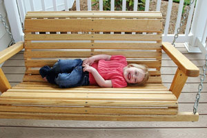 Baby girl relaxing and smiling on a porch swing